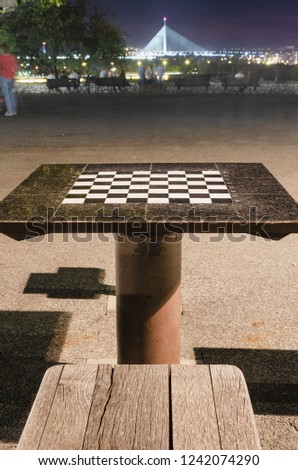 Chess table in the park in the night, big bridge in a distance #1242074290