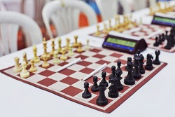 Chess tournament boards ready with chess clock chairs and tables