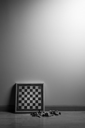 Chessboard leaning against wall with the chess pieces laid out in front.