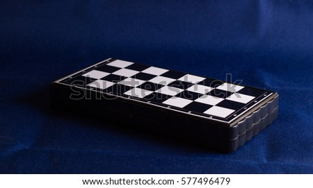 Chessboard on a fabric background, it is a very ancient game invented in India, the cells of the board are placed chess pieces and players start battle #577496479