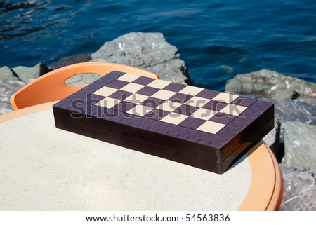 stock-photo-chessboard-on-a-table-by-the-sea-brainstorming-place-54563836.jpg