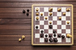 Chessboard on wooden background. Top view with copy space, flat lay