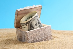 Chest with money american hundred dollar bill on a beach