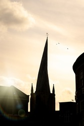 Chesterfield Crooked Spire church silhouette of tower in town centre with sun setting behind and birds in sky cockerel weather vein on top. Historic St Marys parish worship building.