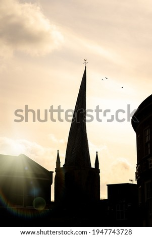 Chesterfield Crooked Spire church silhouette of tower in town centre with sun setting behind and birds in sky cockerel weather vein on top. Historic St Marys parish worship building. Stockfoto ©