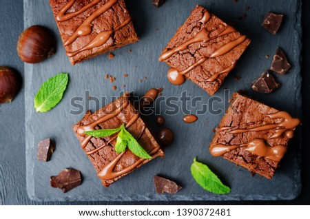 chestnut brownies with chocolate icing on a black background. toning. selective Focus #1390372481