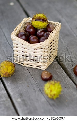 chestnuts and wooden corals in a wicker basket on the garden table