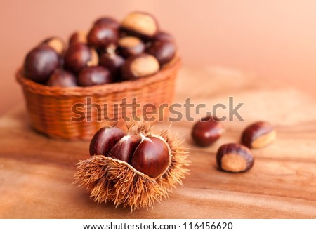 Chestnuts in a basket on wooden table