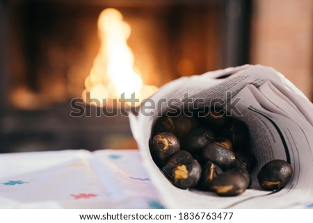 """Chestnuts inside a cone with the fireplace in the background. Making roasted chestnuts at home. Celebrating """"Castanyada, Castañada"""" typical dish and tradition of Catalonia, Spain, in All Saints Day."""