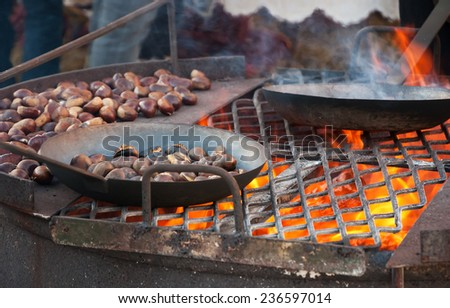 Chestnuts roasted in old iron pans over the fire at traditional Christmas medieval fair in Provins (France). Selected focus on the grill and on the burned chestnuts in the pan.