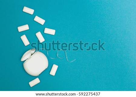 Chewing gum and dental floss on a blue background. Space for text. #592275437