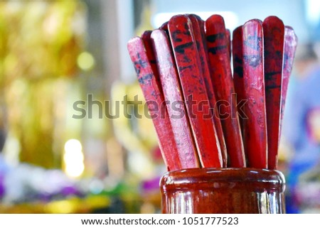 Chi-Chi Sticks or Seam-Si of Chinese traditional on blurred gold and other color background at Thai temple, a tally used in counting one of several sticks in a bamboo cylinder, fortune hope concept