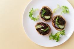 Chia seed sandwiches on pieces of baguette with cucumber, radish and herbs on a white plate on a yellow background. Healthy food concept. Copy space. Top view. Horizontal orientation.