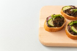 Chia seed sandwiches on slices of bread with cucumber, radish and herbs on a wooden cutting board on a gray background. Vegan food concept. Copy space. Horizontal orientation.