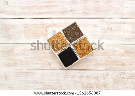 Chia Seeds, Flax Seeds, Sesame Seeds and Black Cumin Seeds on whitewashed wood table