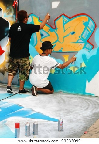 CHIANG MAI, THAILAND - APRIL 7: A young graffiti artist during drawing and painting his 3D artwork in Chiang Mai Fest and Art on the Street 2012, On April 7, 2012 in Chiang Mai, Thailand.