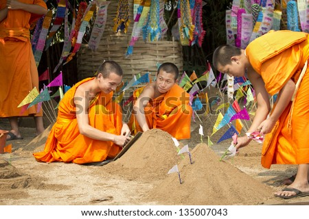 CHIANG MAI THAILAND - APRIL 14 : Songkran festival, Buddhist monk make sand chedi and pin traditional flags . APRIL 14,2013 in Phan-Tao Temple, Chiangmai, Thailand.