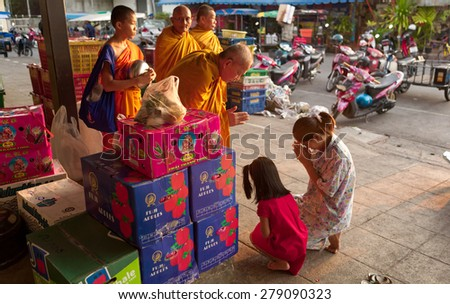 CHIANG MAI, THAILAND - APRIL 16, 2008: Unidentified Buddhist monks receive morning alms and food donations to their temple. Buddhism practices is widely seen and is an important part of life here.