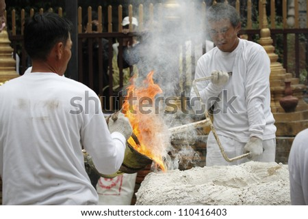CHIANG MAI  THAILAND - AUGUST 12 : Buddhist metal cast ceremony for buddha statue , Pouring molten metal in mold for buddha statue . Aug 12,2012 in Lok Molee Temple, Chiangmai, Thailand.