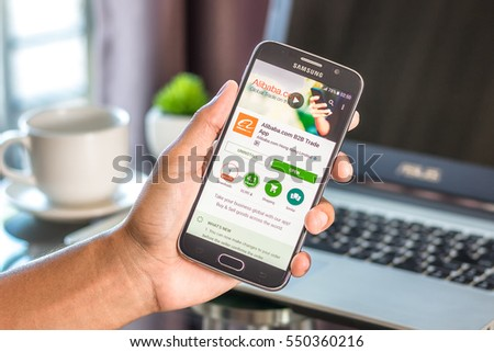 Chiang Mai,Thailand - January 7, 2017 : Asian man holding Samsung Galaxy S6 with alibaba aliexpress app on the screen on desk office. Top view of business workplace.