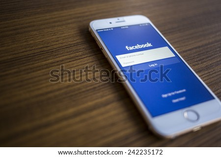 CHIANG MAI THAILAND JANUARY 02 2015 Facebook Login page application on Apple iPhone 6 and wood background Facebook is largest and most popular social networking site in the world
