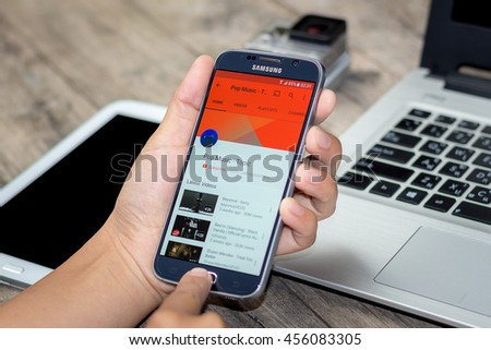 CHIANG MAI,THAILAND - JULY 21, 2016 : Asian Woman holding Samsung Galaxy S6 with youtube app on the screen on Wood desk office. Top view of Business workplace.