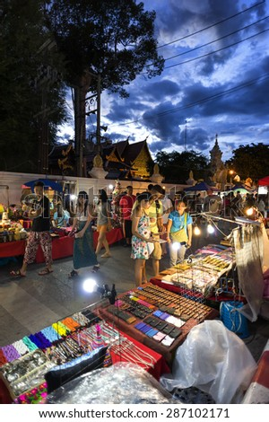 CHIANG MAI THAILAND - JUNE 14 : Sunday market walking street, The city center Thai temple marketing and trading of local tourists come to buy souvenirs. on June 14, 2015 in Chiang Mai, Thailand.