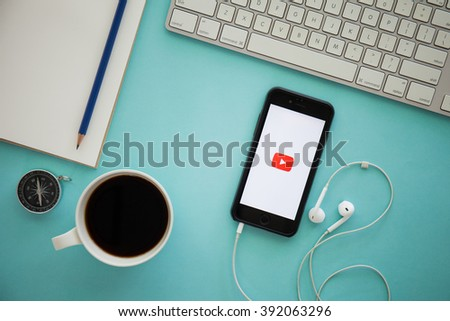 CHIANG MAI, THAILAND - MARCH 17, 2016:Brand new Apple iPhone 6 with YouTube app on the screen lying on desk with headphones. YouTube is the popular online video-sharing website,