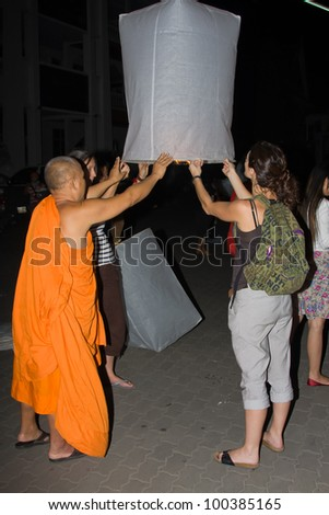 CHIANG MAI, THAILAND - NOVEMBER 11: Monk and girls holding a flying fire lantern to celebrate the Loy Krathong festival in Chiang Mai, Thailand on November 11, 2011
