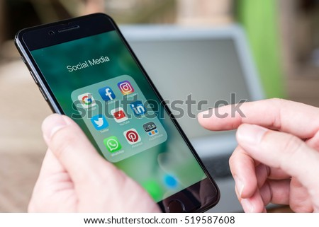 CHIANG MAI, THAILAND - NOVEMBER 14th, 2016: Hand of man using Iphone7 Plus with icons of social media on screen, smartphone life style, smartphone era, smartphone in everyday life