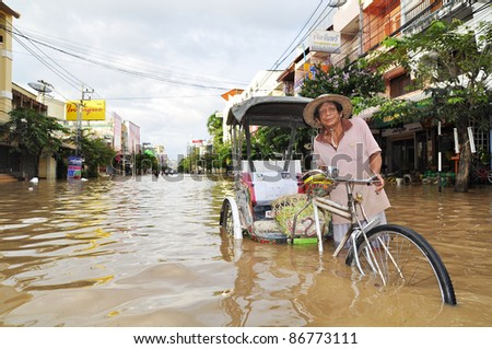 CHIANG MAI THAILAND - SEPTEMBER 30 : Flooding the Chiangmai city.An unidentified elderly man holding a bicycle through the flood on September 30,2011 in Chiangmai Thailand - stock photo