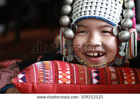 CHIANG RAI, THAILAND - OCT 1 : Akha girl with traditional clothes and silver jewelery in akha hitt tribe minority village on October 1, 2011 in Chiang Rai, Thailand. - stock photo