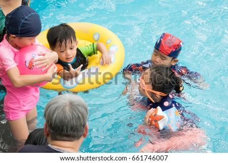 Chiangmai, Thailand - June, 03, 2017 : Swimming trainer teaching children in a swimming pool at Chiangmai, Thailand.