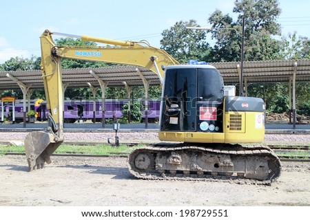 CHIANGMAI, THAILAND - NOVEMBER 15 2013: Private backhoe work for change railroad sleeper from wood to concrete. Work of State railway of thailand.  Photo at Chiangmai Train Station,  Thailand.