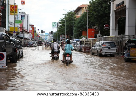 CHIANGMAI , THAILAND - SEPTEMBER 28: Thai monsoon People on motorcycle drive through flooded streets on September 28, 2011 in Chang Karn , Muang , Chiangmai , Thailand.
