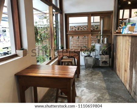 Chiangrai, Thailand; 23 May 2018: Modern cafe interior with a wooden counter and wooden table. This exquisite cafe offers dinner and evening cocktails. The interior design of a Coffee shop, cafe. #1110659804