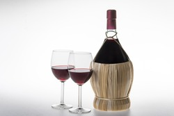 Chianti Bottle, fiasco, and two glasses of red wine on white background