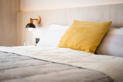 Chic and luxury yellow pillow and white blanket on white oak wooden single bed with bedside hanging lamp in cozy bedroom, Comfy and tasteful bedroom design for everyday living of condo, home.