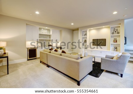 Chic basement features a gray sectional facing a white built-in tv cabinet and wet bar mounted to a wall. Northwest, USA