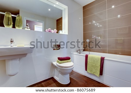 Chic contemporary bathroom suite with brightly coloured towels and large mirror