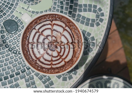 Chic design on hot coffee in white hot coffee mug, placed on a ceramic table. The backdrop of a waterfall, lush greenery, and steam floated out to make it look fresh. Zdjęcia stock ©