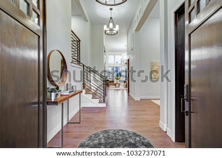 Chic entrance foyer with high ceiling and white walls. New Custom built home interior.
