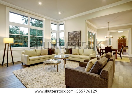 Chic light living room design with dark floors. Furnished with glass top accent tables and beige sofas topped with brown pillows . Northwest, USA  #555796129