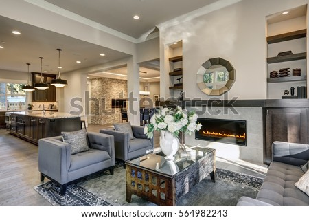 Chic living room filled with built-in cabinets flanking round mirror atop grey tile fireplace, tufted sofa facing two armchairs and window wall overlooking  lush outdoors. Northwest, USA #564982243