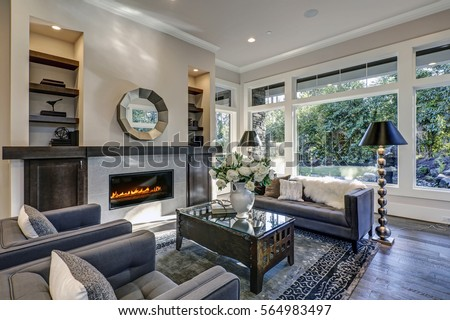 Chic living room filled with built-in cabinets flanking round mirror atop grey tile fireplace, tufted sofa facing two armchairs and window wall overlooking  lush outdoors. Northwest, USA #564983497