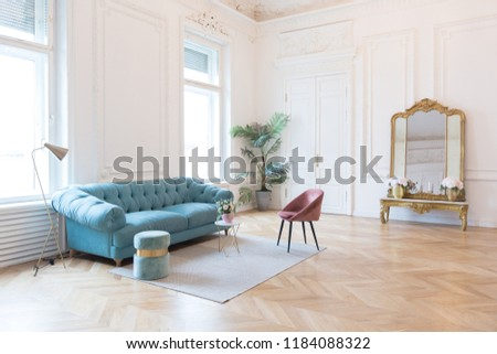 chic spacious light room in an old mansion in the classical style of the 19th century with a high ceiling decorated with stucco on white walls