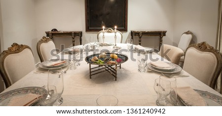 Chic table prepared for the Passover party with the Passover Seder dish in the center. In the background a redecorated frame.