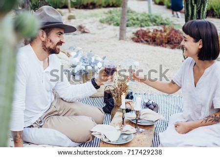 Chic trendy couple of young hipster lovers enjoy day out on romantic date, setup in summer park, enjoying wine and delicious treats and snacks, relationship goals #717429238