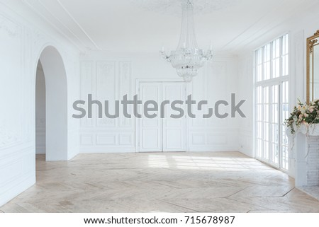 chic white huge spacious hall with a minimum of expensive antique furniture. Baroque interior design with ornament on the walls and parquet on the floor. #715678987