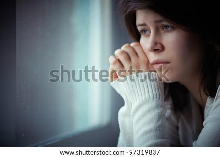 chica triste cerca de una ventana pensando en algo - stock photo